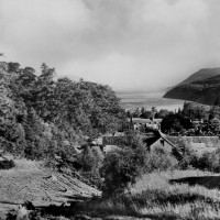 View of Loch Ness from above Foyers Mains Steading buildings .  Possibly taken around the nineteen fifties  notice the corn stooks on the lower left  Photograph courtesy of Alister Chisholm