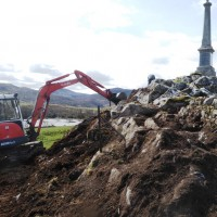 19 April Bob Main with digger scraping the gorse roots of the outcrop . Photograph courtesy of Alister Chisholm